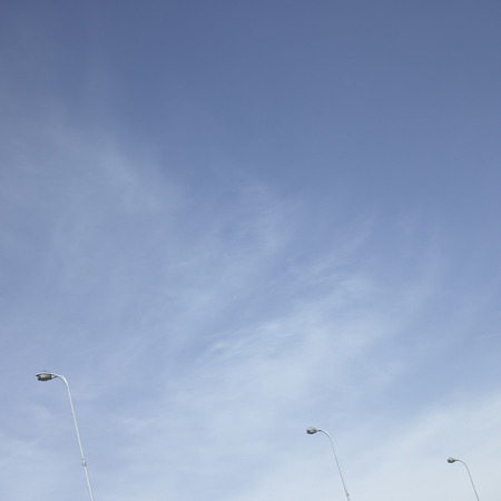 upright row: Streetlights towering up into a cloudy blue sky