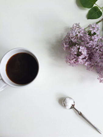 Black coffee in a cup, sugar on a spoon and fresh lilac flowers Standard-Bild