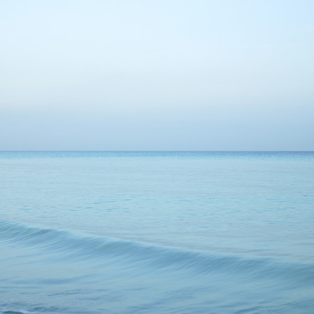 Beautiful turquoise wavy ocean with blue sky