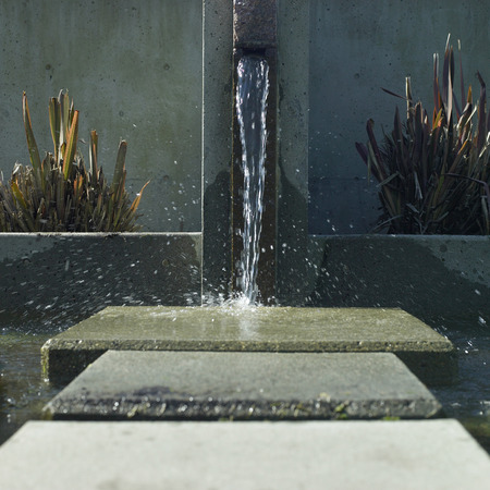 Water spout pours into an urban water feature Stock Photo