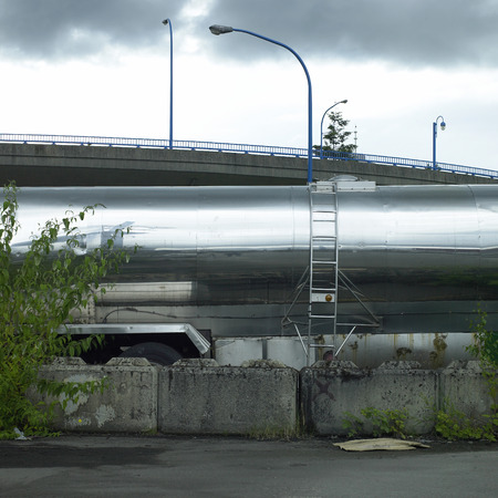 Shiny chrome tanker trailer with side ladder parked near a bridge