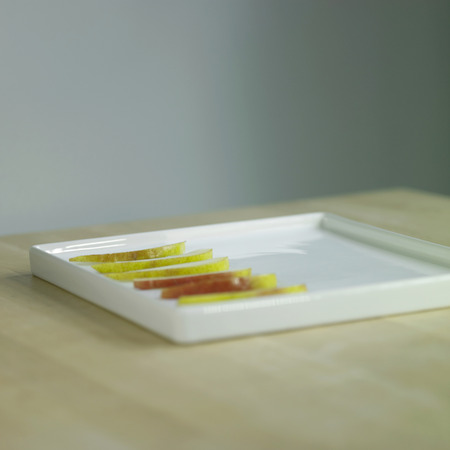 Perfect slices of a pair line half of a white square plate on a chopper's block counter top