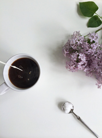 Milk pouring into coffee with sugar spoon and fresn lilac flowers Standard-Bild