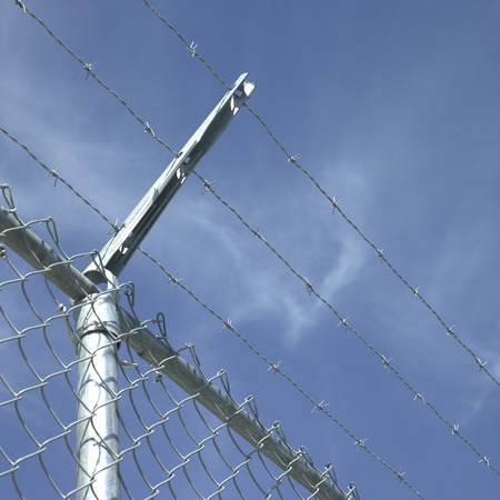 barrier: Chainlink fence with barbed wire top barrier