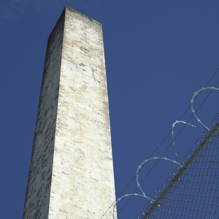 barbed wire fence: Tall brick chimney behind barbed wire fence