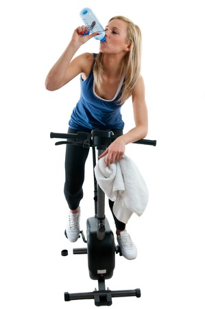 Sliming girl training on the bike and drinking water photo
