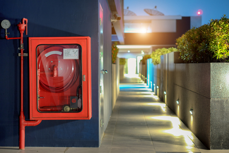 Fire Safety Concept, Fire extinguisher and fire hose reel in public building corridor Stockfoto