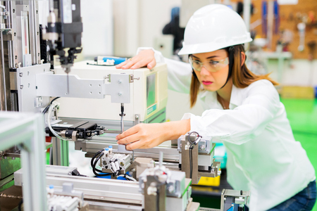 bella bella componentistica fabbrica di fresatrici personale femminile con pinze in possesso di parti di lavorazione.