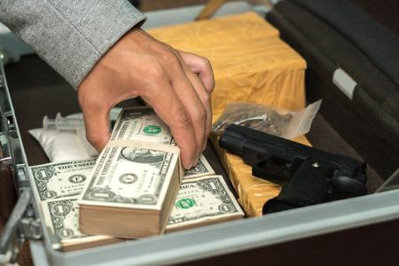 Trafficante di droga che tiene un sacco di soldi in mano e usa la pistola che spinge droga al cliente nello spaccio di droga, concetto sul problema della droga