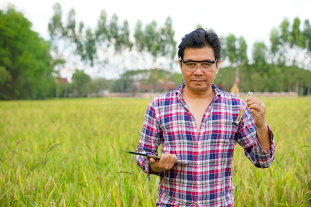 Smart farming.Young Asian male agronomist or agricultural engineer observing green rice field with laptop for the agronomy research. Agriculture and technology concepts