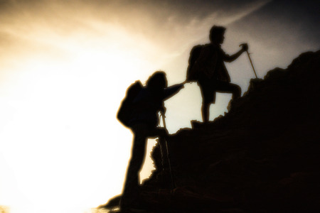 The joint work teamwork of two people man and girl travelers help each other on top of a mountain climbing team, a beautiful sunset landscape. 版權商用圖片