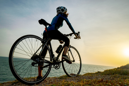 Young sporty lady standing with bicycle on top of a mountain