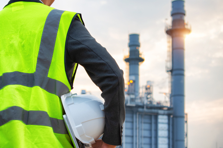 engineering man with white safety helmet standing in front of oil refinery building structure in heavy petrochemical industry 版權商用圖片