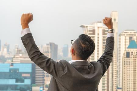 Asian businessmen raise their hands