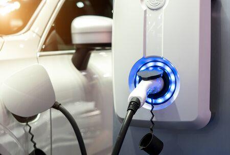 Stromversorgung zum Laden von Elektroautos. Ladestation für Elektroautos. Nahaufnahme des Netzteils, das an ein aufgeladenes Elektroauto angeschlossen ist.