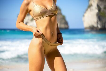 Body part of slim and sporty young girl over ocean background. Traveling and vacation concept.