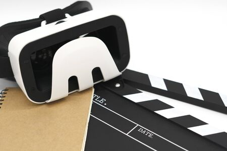 Movie clapper board, notebook and  virtual reality glasses on white background. Concept of equipment for making movies.