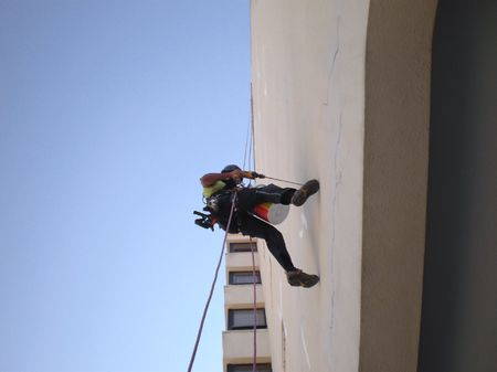 Drilling Building Exterior using ropes photo