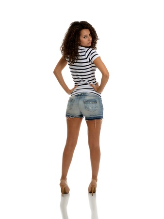 A portrait of sexy brunette posing in jeans shorts and marine top Stock Photo - 14210594