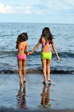 Two young girls walking to the water  photo