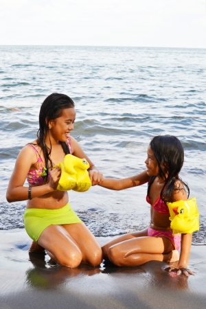 Teen girl helping her younger sister to wear arm band of water safety  photo