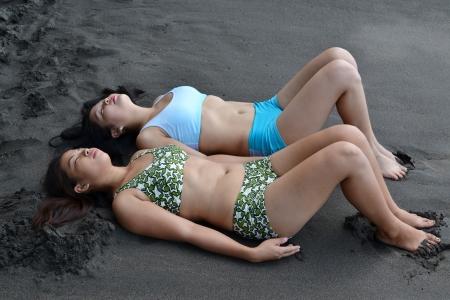 Two Asian Beauty Sleeping on the Beach photo