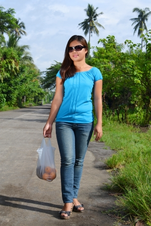 filipina: A beautiful Asian lady walking in a countryside with fresh fruit Stock Photo