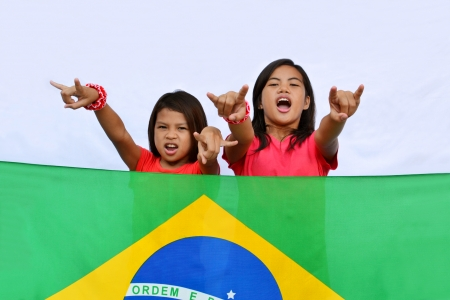 Two native young Brazilian girls supporting their country standing behind a national flag outdoor