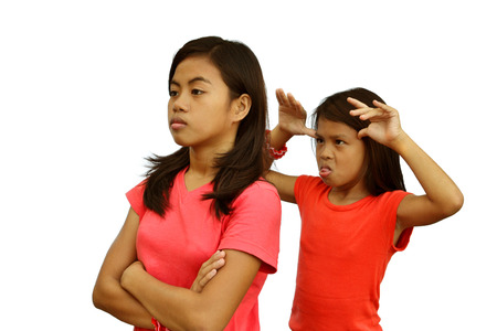 A teenage girl angry with her rude younger sister Stock Photo - 24736441