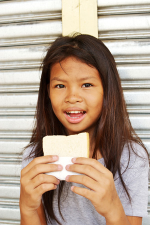 Poor homeless girl happy with a sandwich