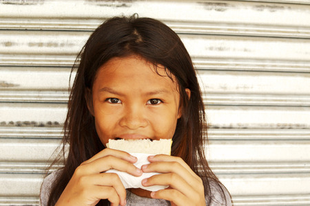 vagabundos: Pobre chica sin hogar feliz con un bocadillo