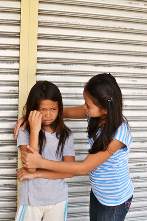 Young lady comforting a homeless sad girl in the street. Stock Photo