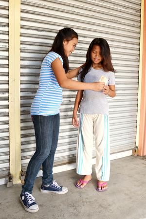 bondad: Se�ora asi�tica joven ayuda pobre ni�a en la calle d�ndole un bocadillo
