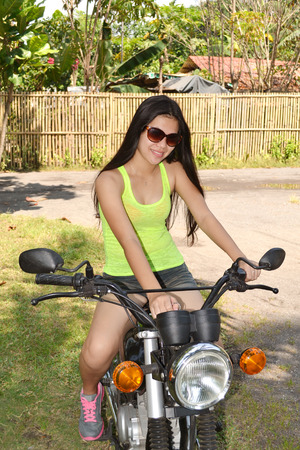 Beautiful Asian biker starting her motorbike in a tropical island photo