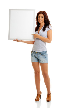 Beautiful caucasian brunette pointing to a white billboard Stock Photo