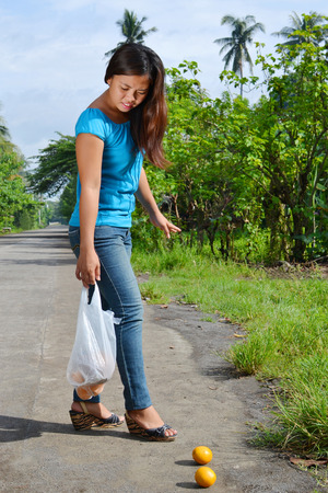 A pretty Asian lady stop to pick up the fallen oranges from her shopping bag on the road