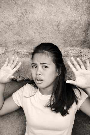 Shocked Asian young lady leaning on a wall with the hands up in a poor area looking at something with fear