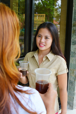 Two female workers having a conversation during a coffee break in the installations of the company
