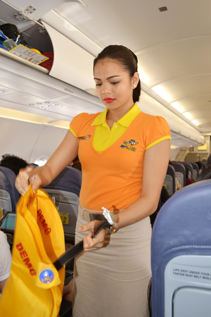 DAVAO PHILIPPINES  APRIL 19 2015: Cebu Pacific flight attendant demonstrating safety measures for the passengers. Safety demonstration is a must by aviation law.