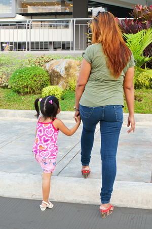 go shopping: Little girl crossing the street hand in hand with her mother to go shopping