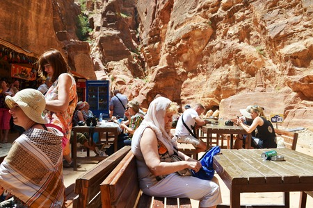 Petra, Jordan - May 19, 2015: Tourists in the service area enjoying drinks  free wifi right in front of the treasury of Petra. Petra is one of the seven wonders of the world.