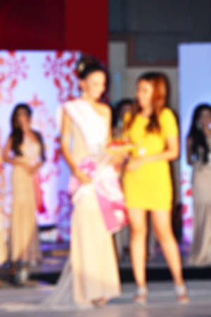 Blurred background of a crowned beauty pageant contestant on a stage