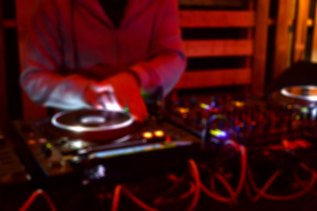 Blurred background of a DJ playing music in a party Stock Photo