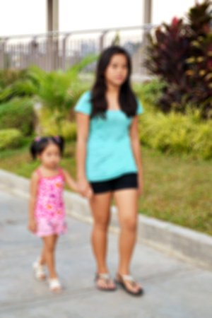 Blurred background of a young lady holding the hand of her little sister on a public sidewalk