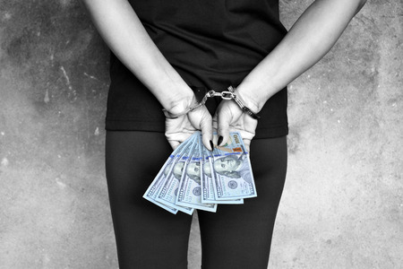 Female thief cuffed hands with US dollars in her hands Stock Photo