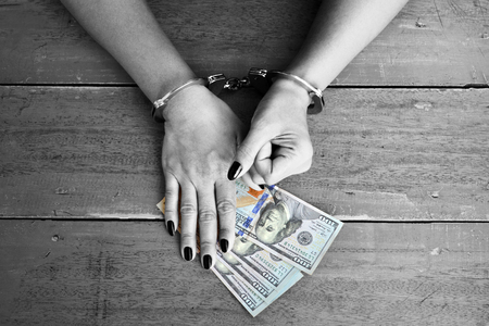 A female with hands cuffed and US dollars on the table Stock Photo