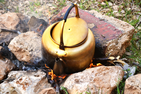 Golden old kettle to boil water on wood fire while camping Stock Photo