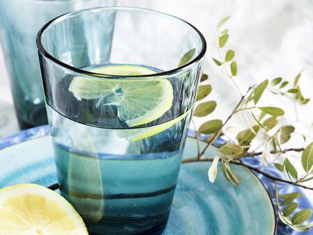 Un verre d'eau pure et fraîche avec une tranche de citron sur une assiette turquoise, une bonne boisson pour l'hydratation