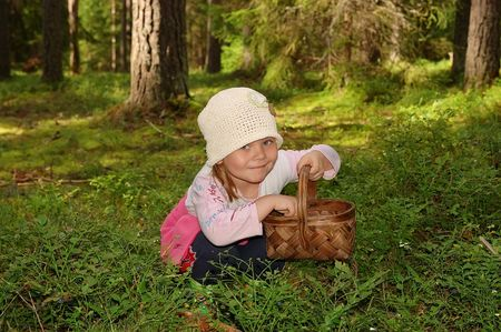 The girl in the forest, collecting berries in a basket