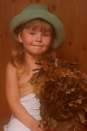 The smiling little girl with a broom in a sauna Stock Photo